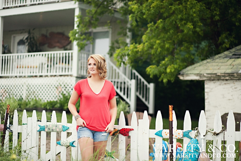 girl against a picket fence beach senior pictures